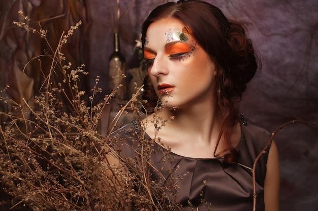 乾いた枝と明るいメイクアップを持つ女性