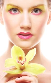 Молодая женщина с ярким макияжем держит орхидею