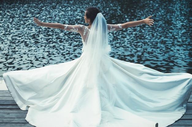 Красивая невеста на открытом воздухе возле озера.