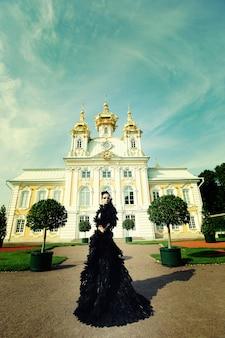 宮殿の隣にポーズ黒のドレスで美しい女性。