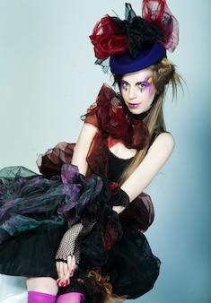 創造的なメイクとカーニバルドレスの若いモデル。