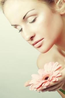 ガーバーの花を持つ若い女