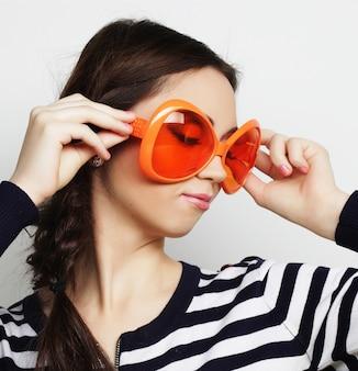 大きなオレンジ色のサングラスを持つ若い女性