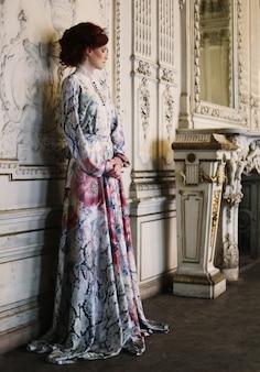 宮殿の部屋に立っている美しい女性。