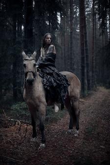 暗い森で馬と長い髪の若い男。