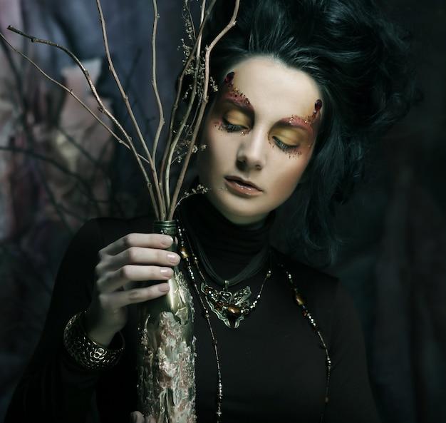 暗い枝を持つ女性が乾いた枝で補います