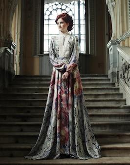 階段でポーズのエレガントなドレスを着た女性