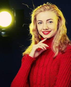 赤いセーターで笑顔金髪