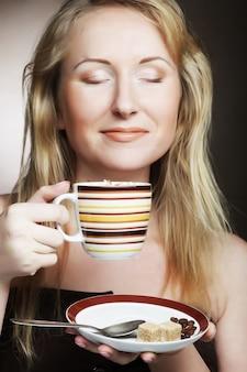 Красивая женщина пьет кофе