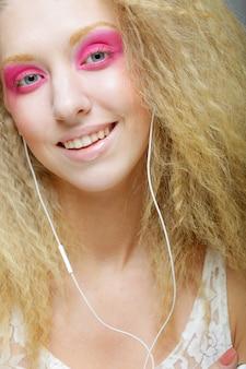 彼女のヘッドフォンで音楽に合わせて踊る若い女性