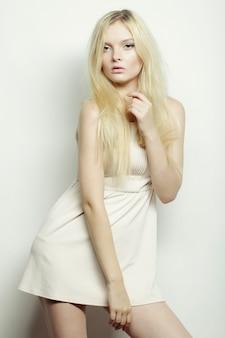 スタジオでポーズをとって白いドレスのファッションブロンド女性