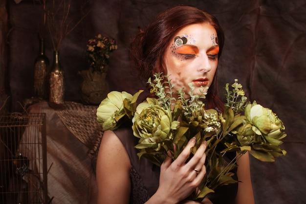 緑の花を持って明るく創造的なメイクアップを持つ女性