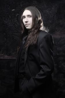 Портрет модной мужской модели с длинными волосами