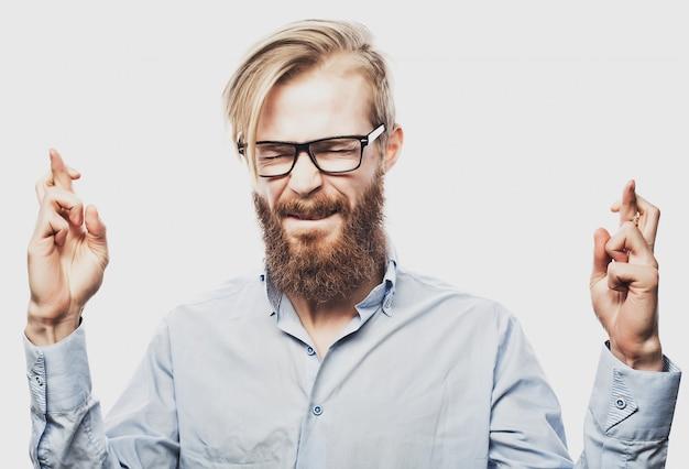 若いひげを生やした男の指を交差させる