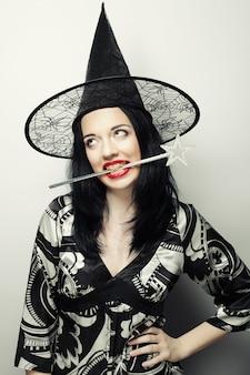 面白い魔女。キャニバルハットを持つ若い幸せな女。
