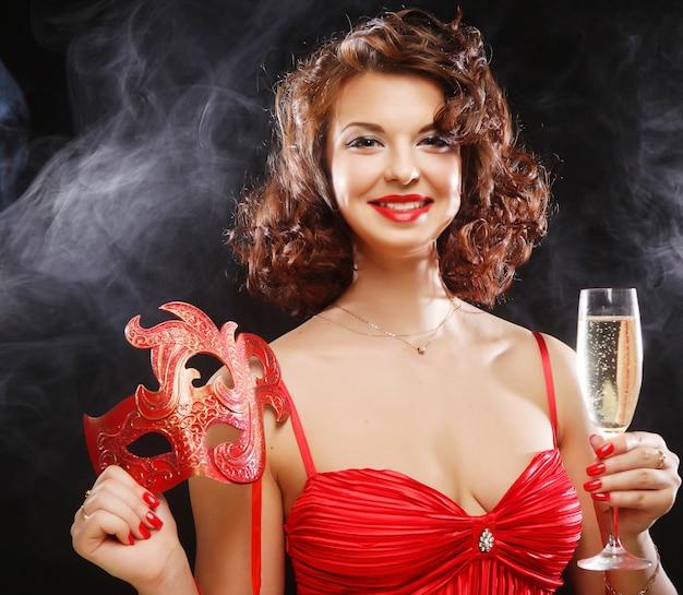 マスクとカーニバルで赤いドレスを着た女性