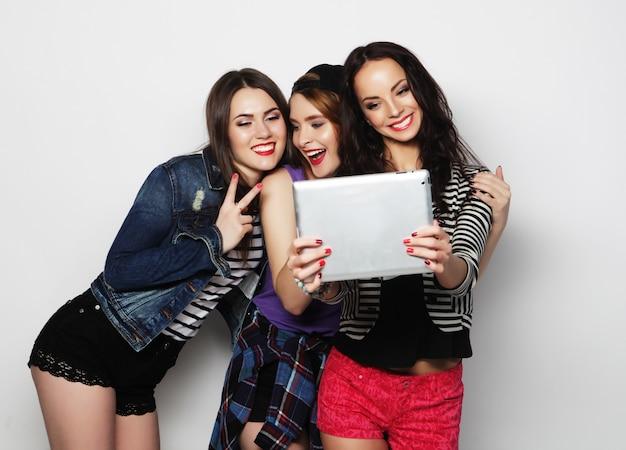 Друзья девушки принимая селфи с цифровым планшетом