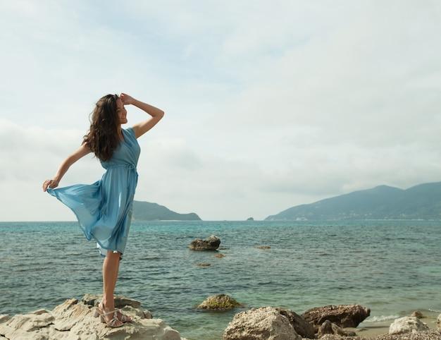 若い幸せな女が海の近くでポーズ