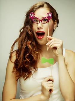 パーティーメガネを保持している遊び心のある若い女性。
