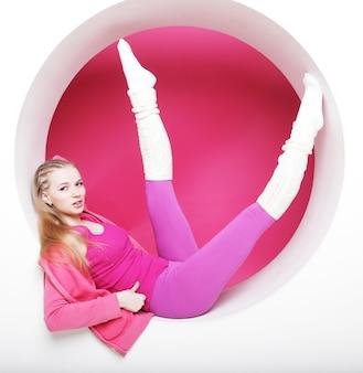 スポーティな女性がピンクの円でポーズ