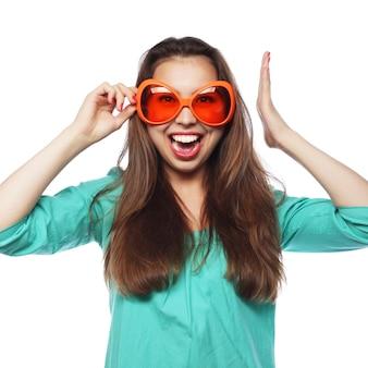 パーティーメガネで遊び心のある若い女性。良い時間の準備ができています。