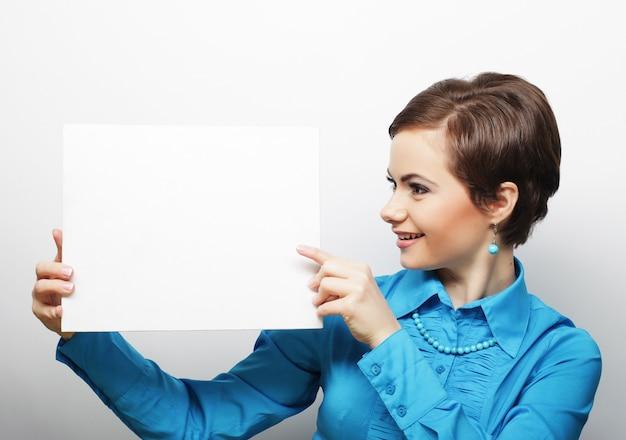 Молодая вскользь женщина счастливая держа пустой знак