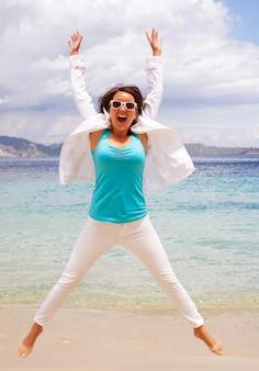 Счастливая девушка прыгает на пляже