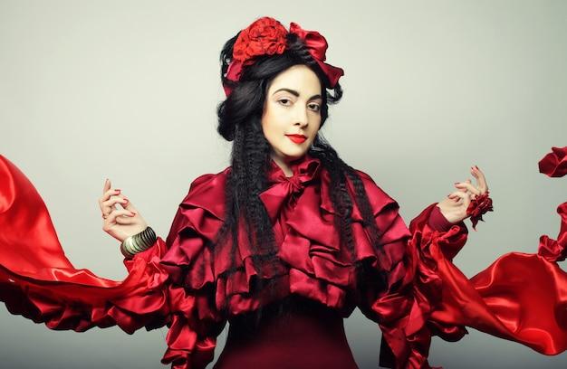 赤い帽子とエレガントな赤い衣装の女性。