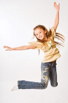 白い背景の上の少女ジャンプ