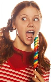 キャンディーポップを保持しているかなり若い女性。クリスマスツリー。