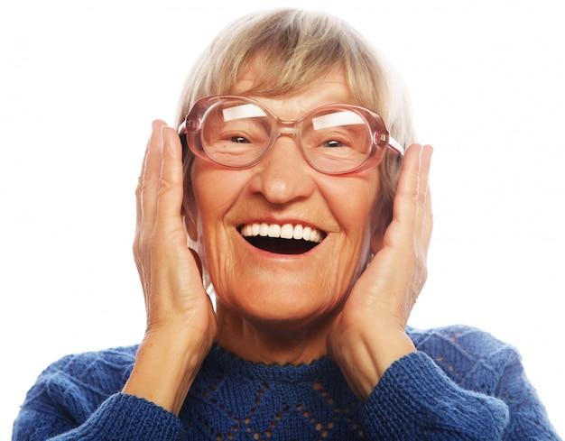 カメラを見て幸せな驚きの年配の女性