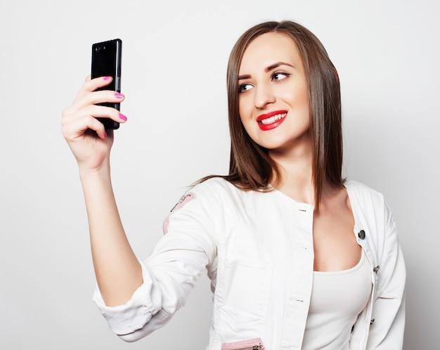 Милая молодая женщина используя мобильный телефон