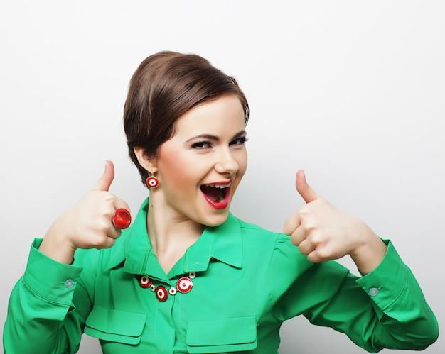 Успешная девушка дает большой палец двумя руками
