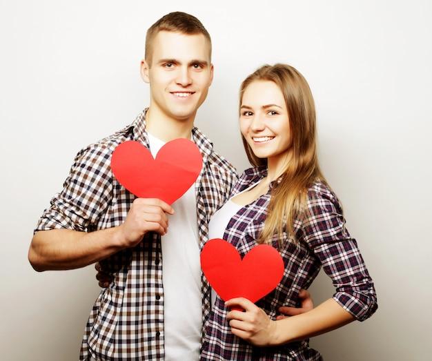赤いハートを保持している愛の幸せカップル。