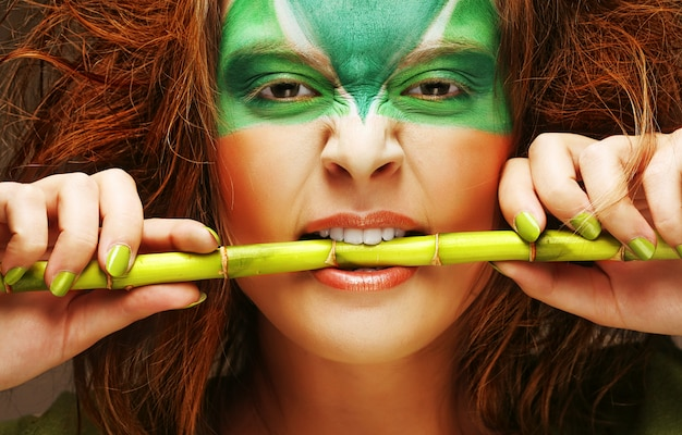 竹、創造的なメイクの女性