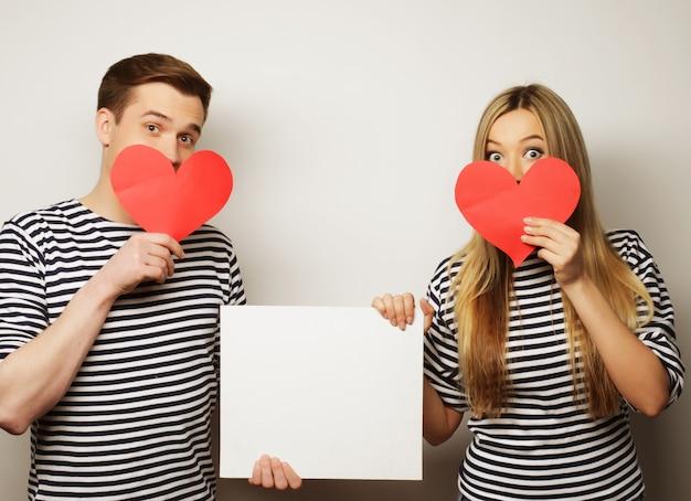 白い空白と赤の心を持って幸せなカップル。