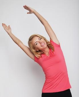 Женщина осуществляет йогу с ее руки над головой