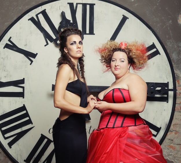 Две королевы позируют рядом с часами.