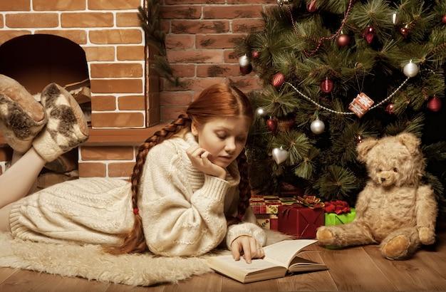 クリスマスツリーの前で本を読む女