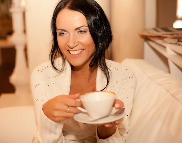Красивая улыбающаяся женщина пьет кофе