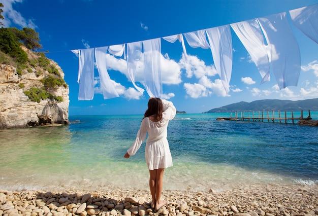 Женщина в белом платье стоя на пляже