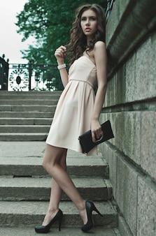 若い女性のドレスを着て、通りを歩いて