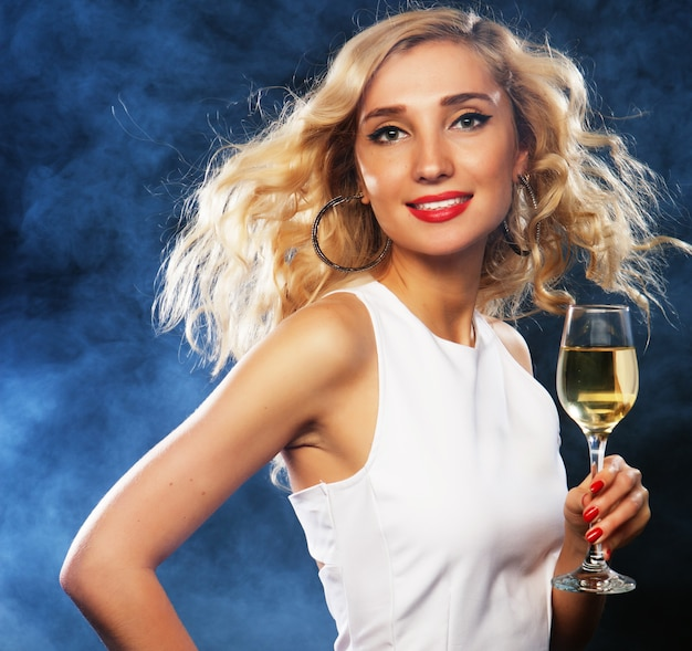 スパークリングワインのグラスとイブニングドレスの女性