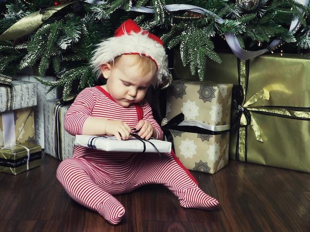 クリスマスツリーを飾る近くのギフトボックスと小さな女の赤ちゃん