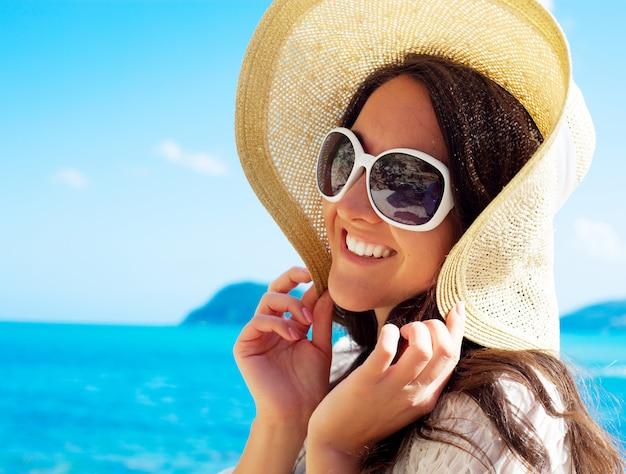 ビーチで帽子で幸せな女