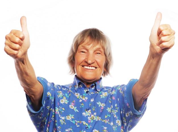 Старая женщина показывает знак ок на белой стене