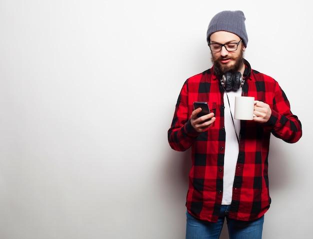 Молодой бородатый человек с мобильным телефоном