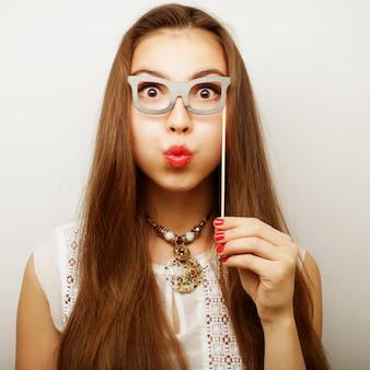 Игривая молодая женщина, держащая партийные очки.