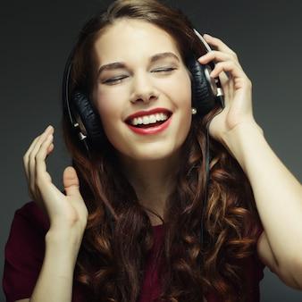 Молодая женщина в наушниках слушает музыку