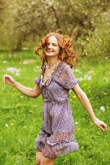 庭でリラックスしたドレスの若い女性